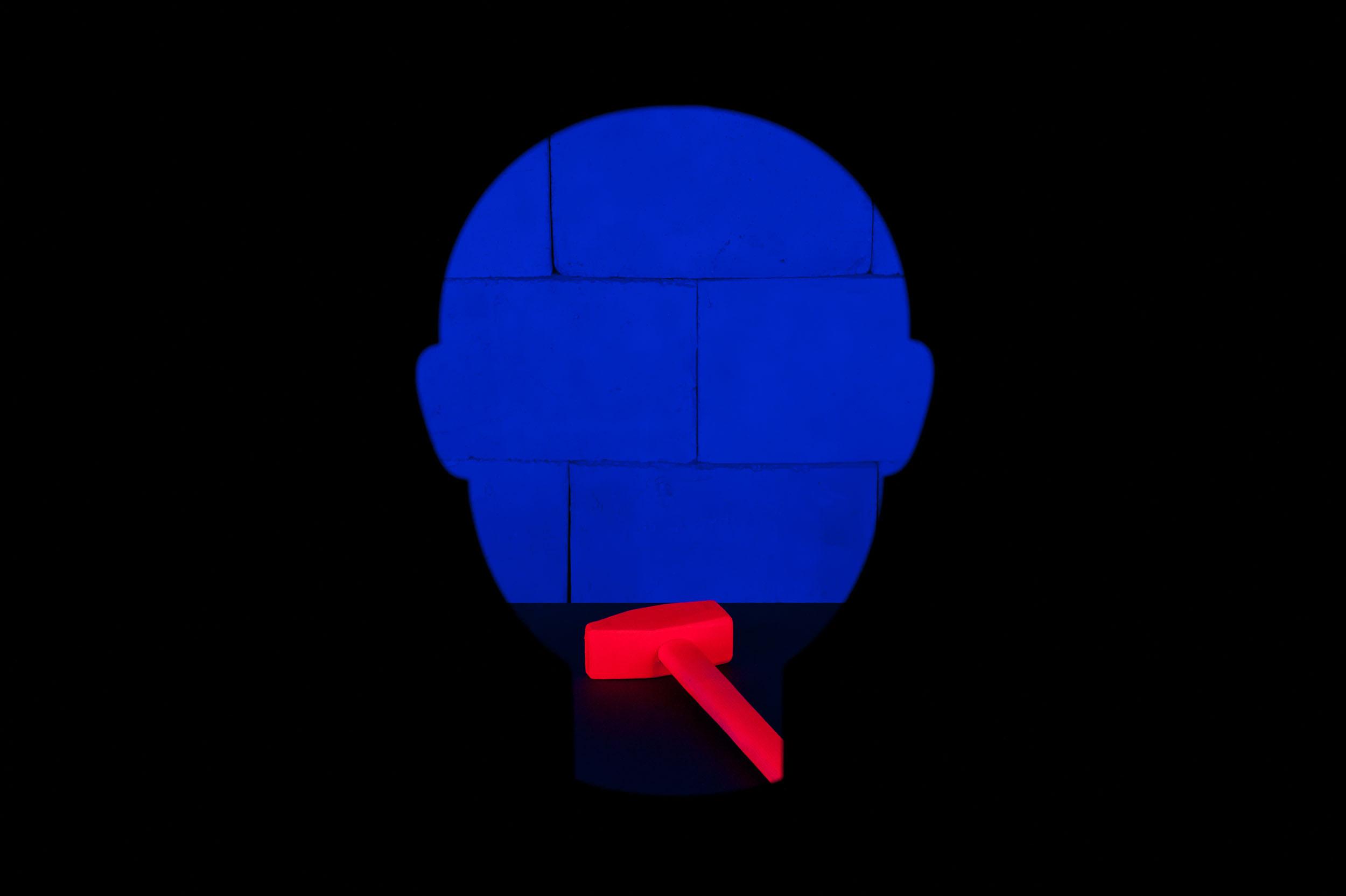 Orangefarbener Vorschlaghammer und blaue Mauer im Neonlicht, innerhalb kopfförmiger Silhouette