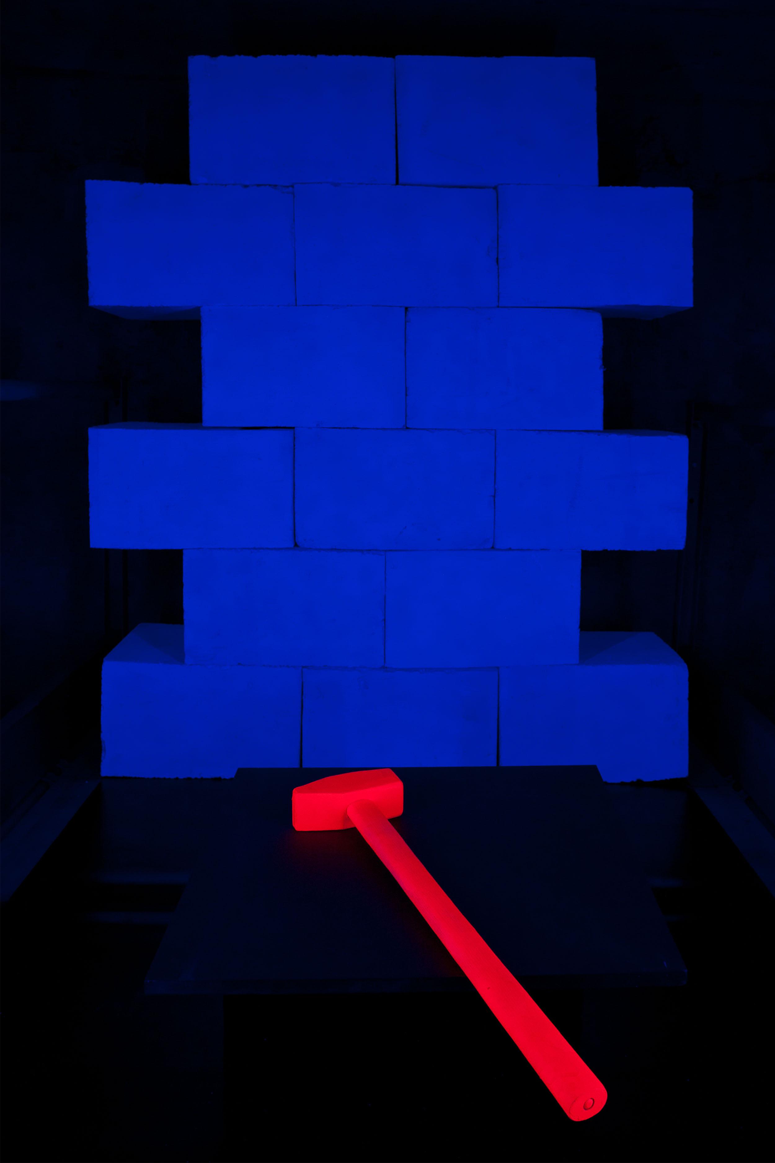 Orangefarbener Vorschlaghammer und blaue Mauer im Neonlicht
