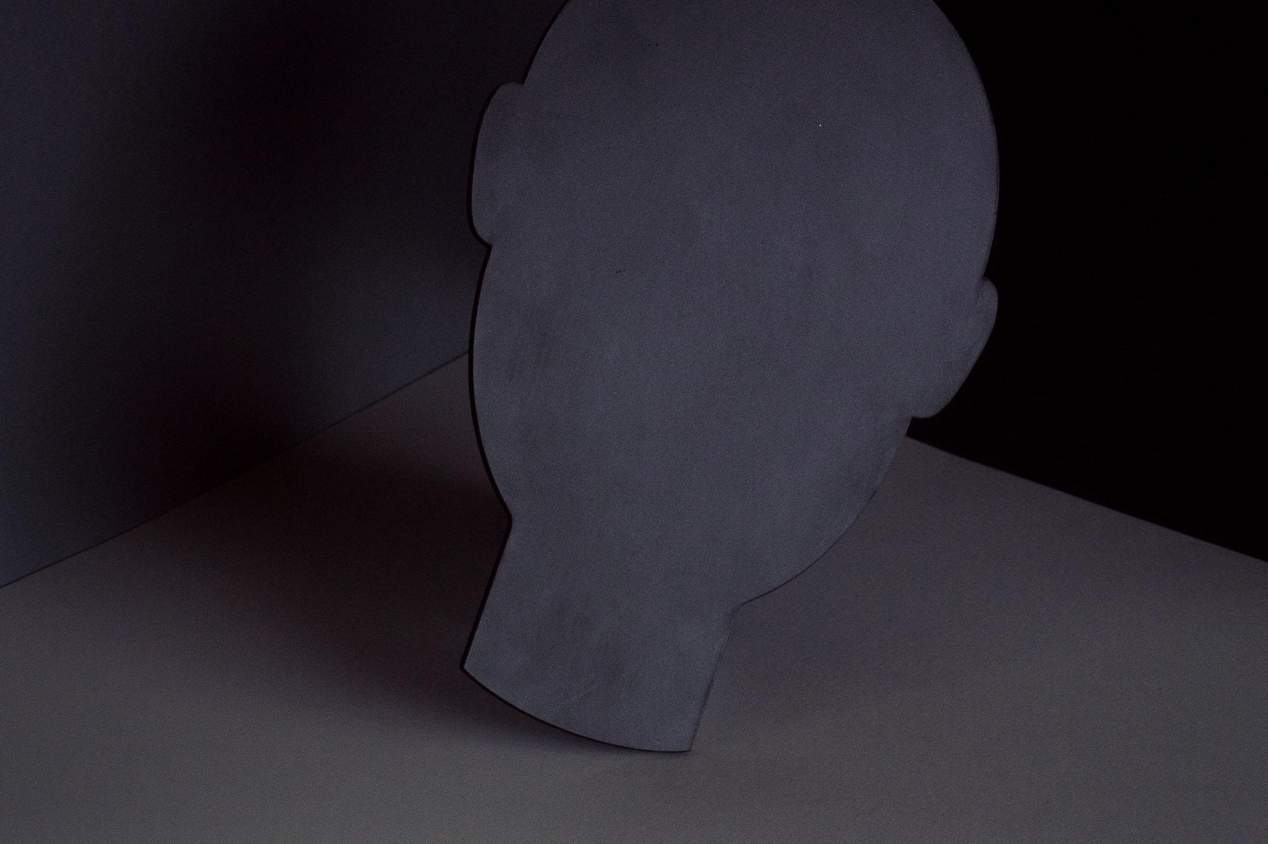 Schwarze, kopfförmig gefräste Kunststoffplatte vor schwarzem Hintergrund