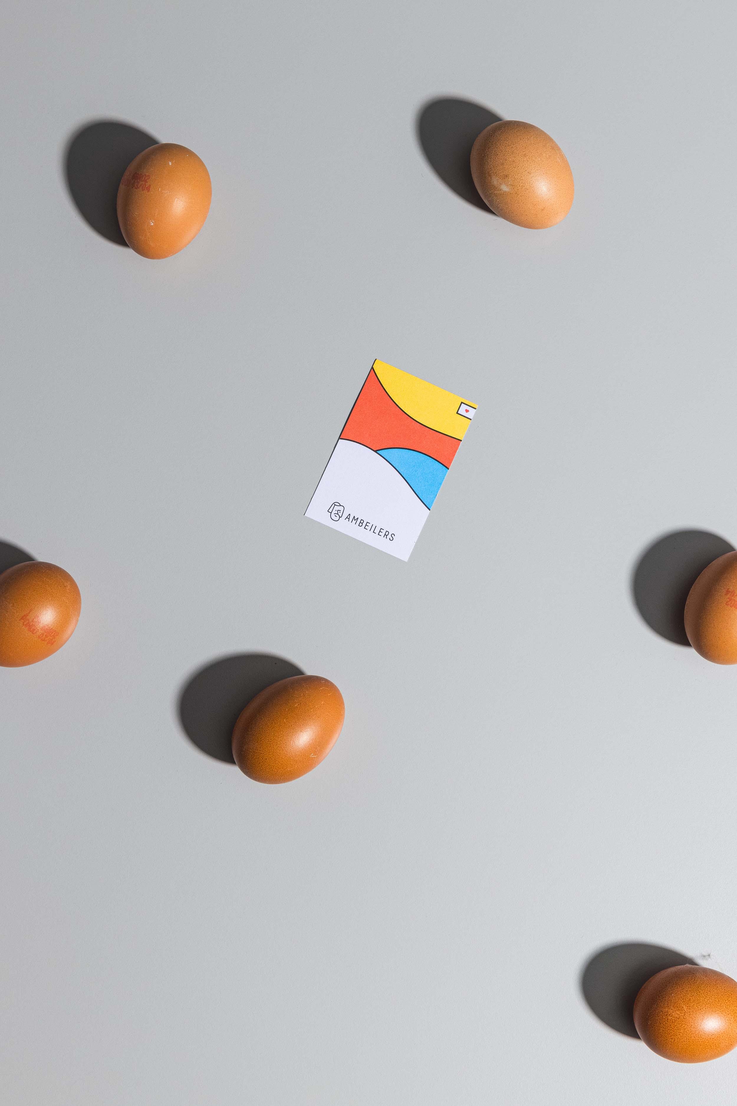 Sechs braune Eier und Vorderseite der Visitenkarte mit farbigem Visual und Logo für Ambeilers, liegend auf grauem Hintergrund