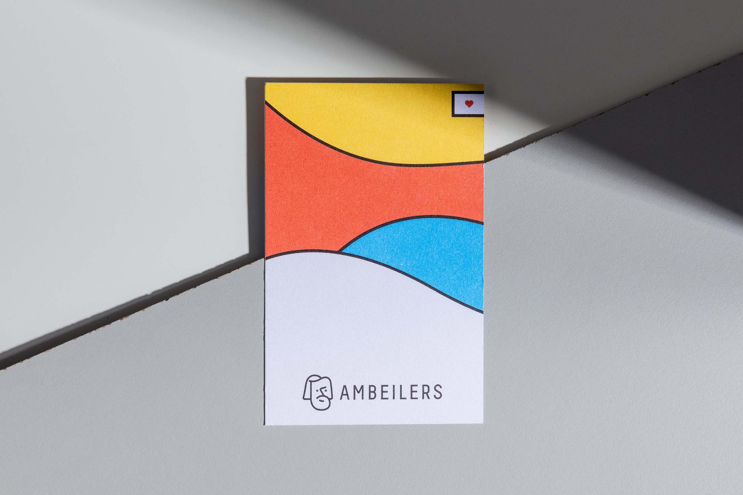 Vorderseite der Visitenkarte mit farbigem Visual und Logo für Ambeilers, liegend auf grauem Hintergrund