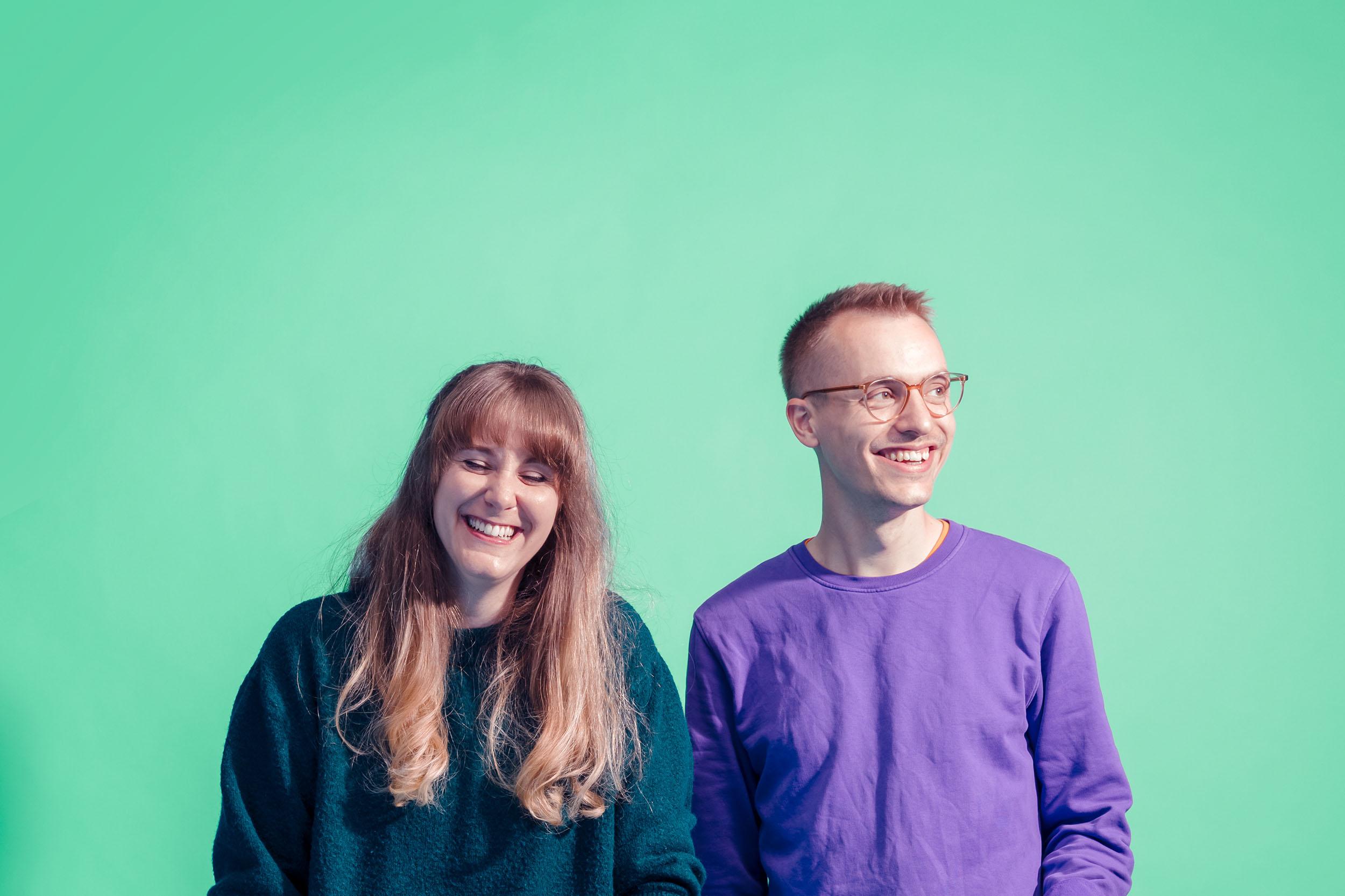 Porträt von Aline Cadonau und Simon Heger, lachend vor grünem Hintergrund