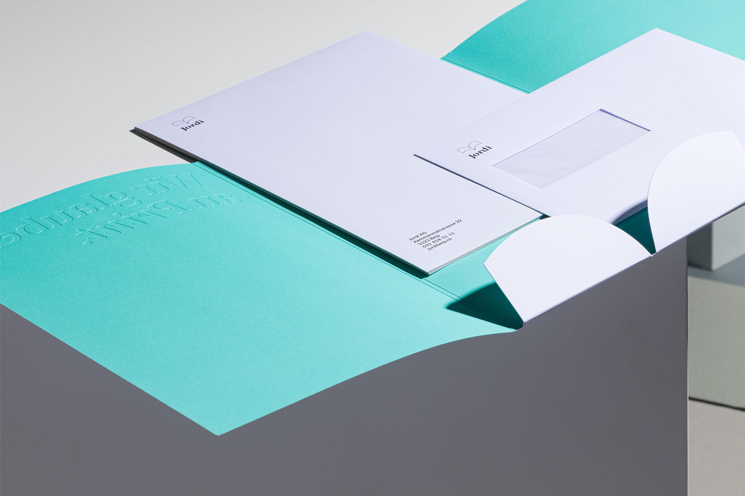 Aufgeklappte, türkisfarbene Dokumentenmappe mit weissem Briefpapier und Kuvert C5 für Jordi AG, liegend auf weissem Kubus