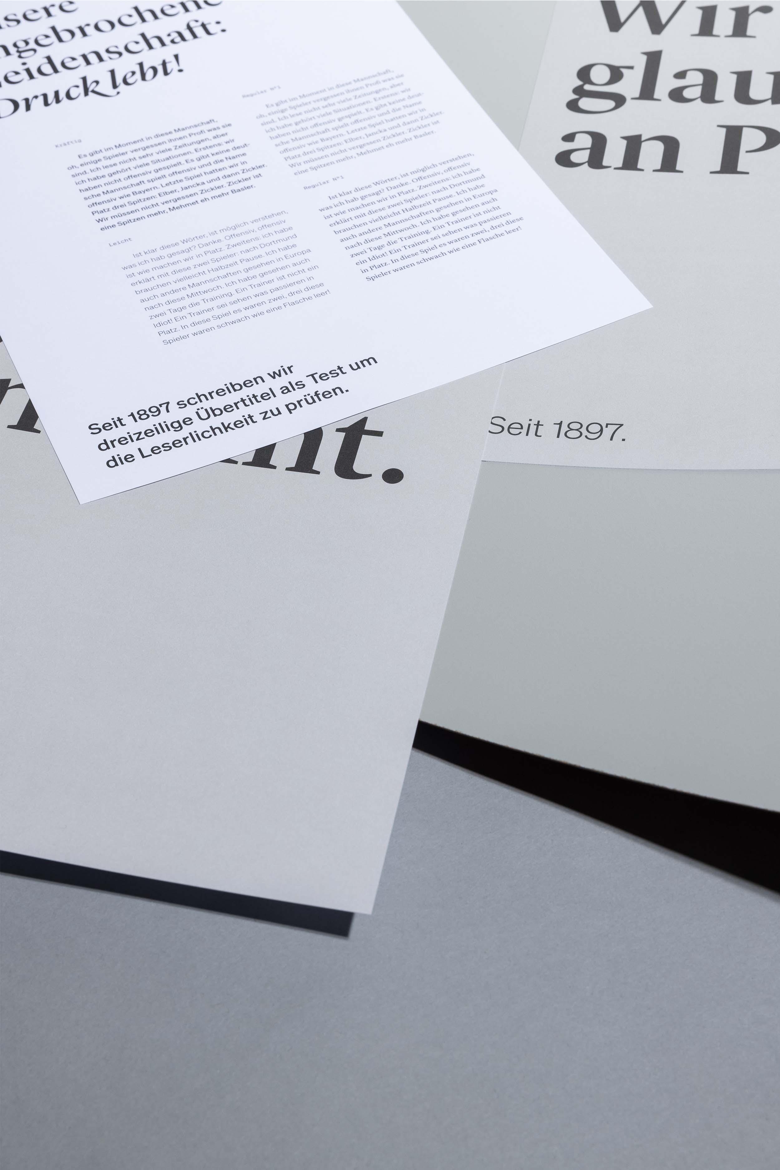 Papierbogen mit Schrift- und Farbtests für Jordi AG, wild übereinander liegend auf grauem Hintergrund