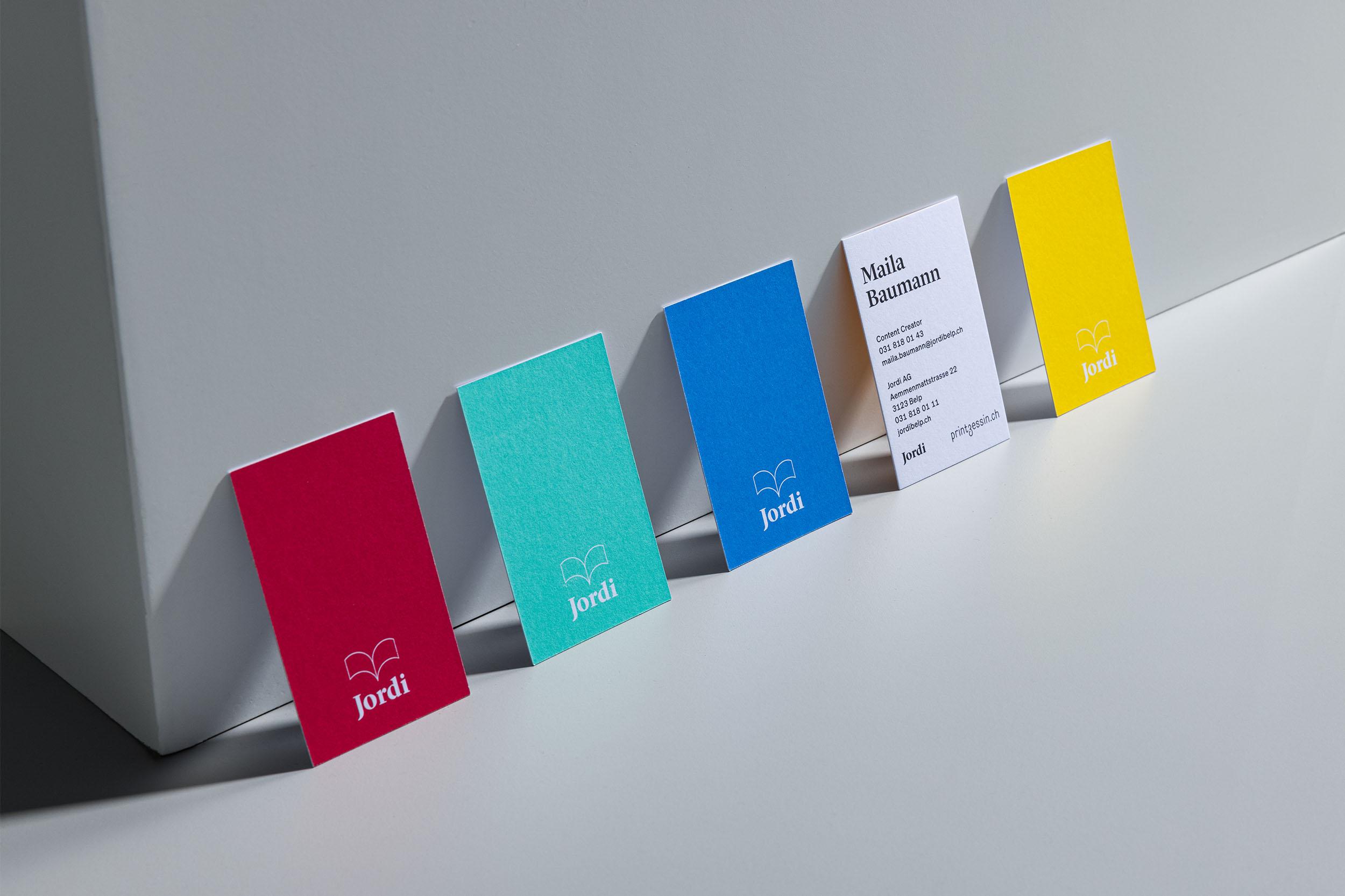 Vorder- und Rückseiten der Visitenkarte in verschiedenen Farbvarianten für Jordi AG, nebeneinander an weissen Kubus anlehnend