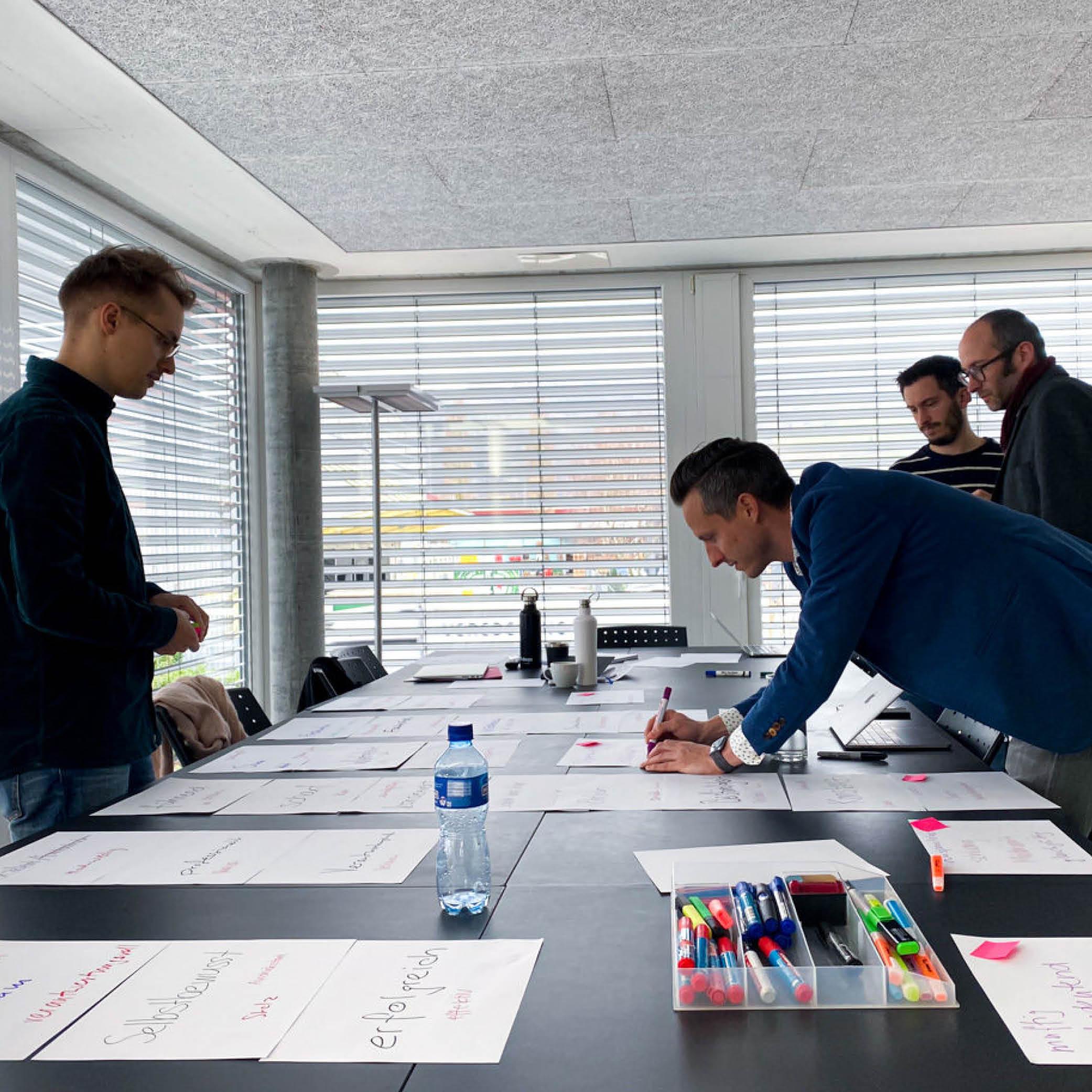 Vier Personen machen auf dem Tisch eine Auslage mit Papieren eines Workshops