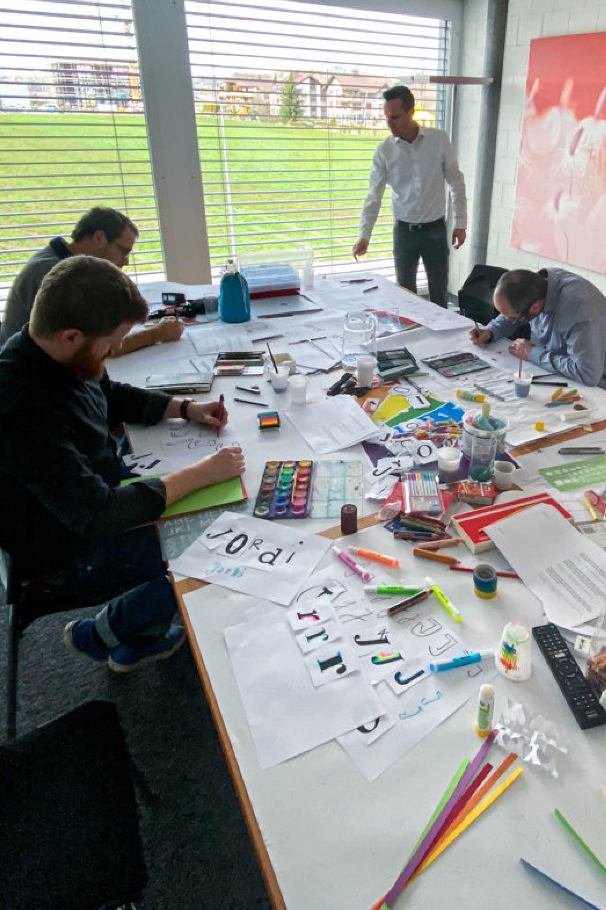 Vier Personen zeichnen an einem von Workshopmaterial bedeckten Tisch