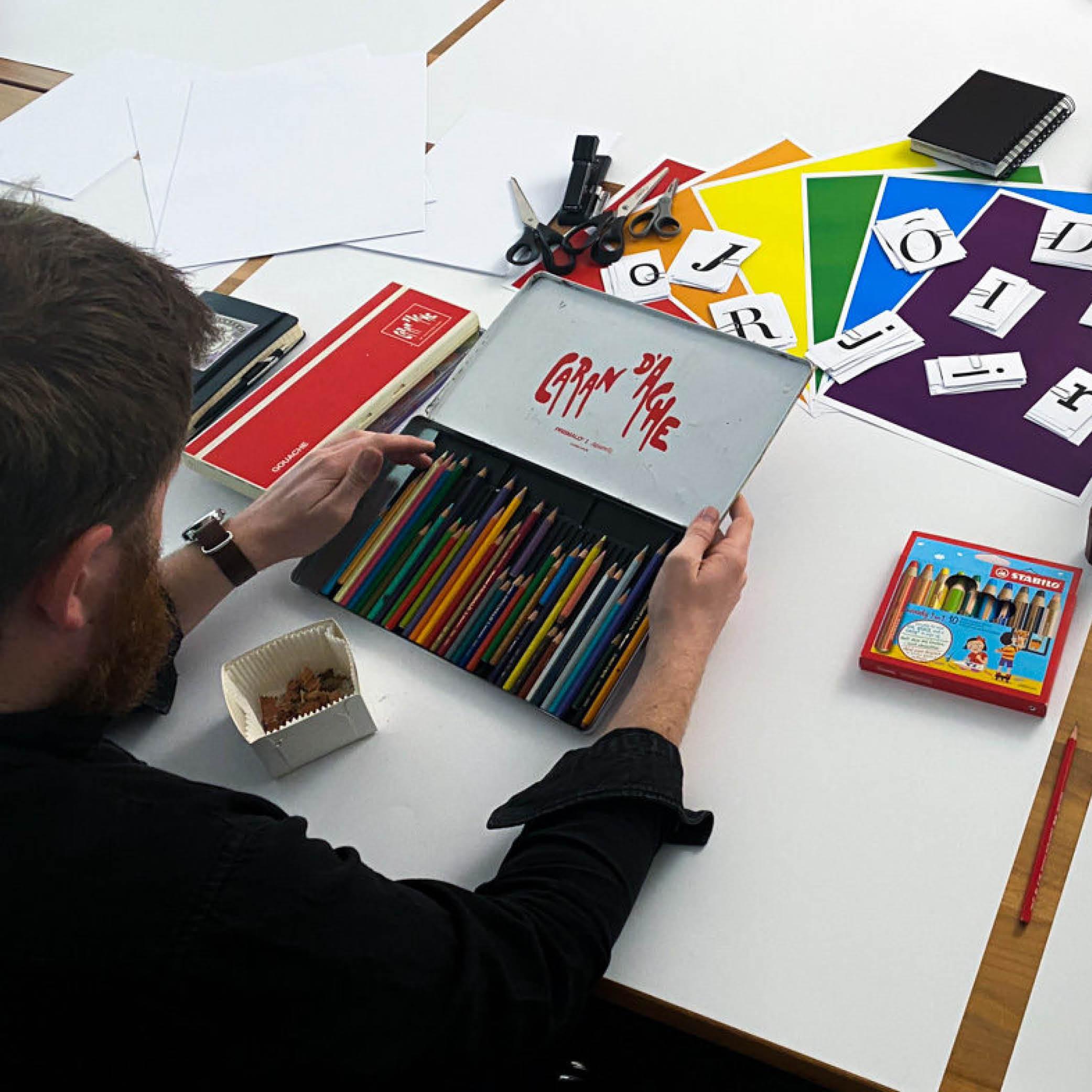 Person öffnet Farbstiftschachtel auf Tisch mit Workshoputensilien