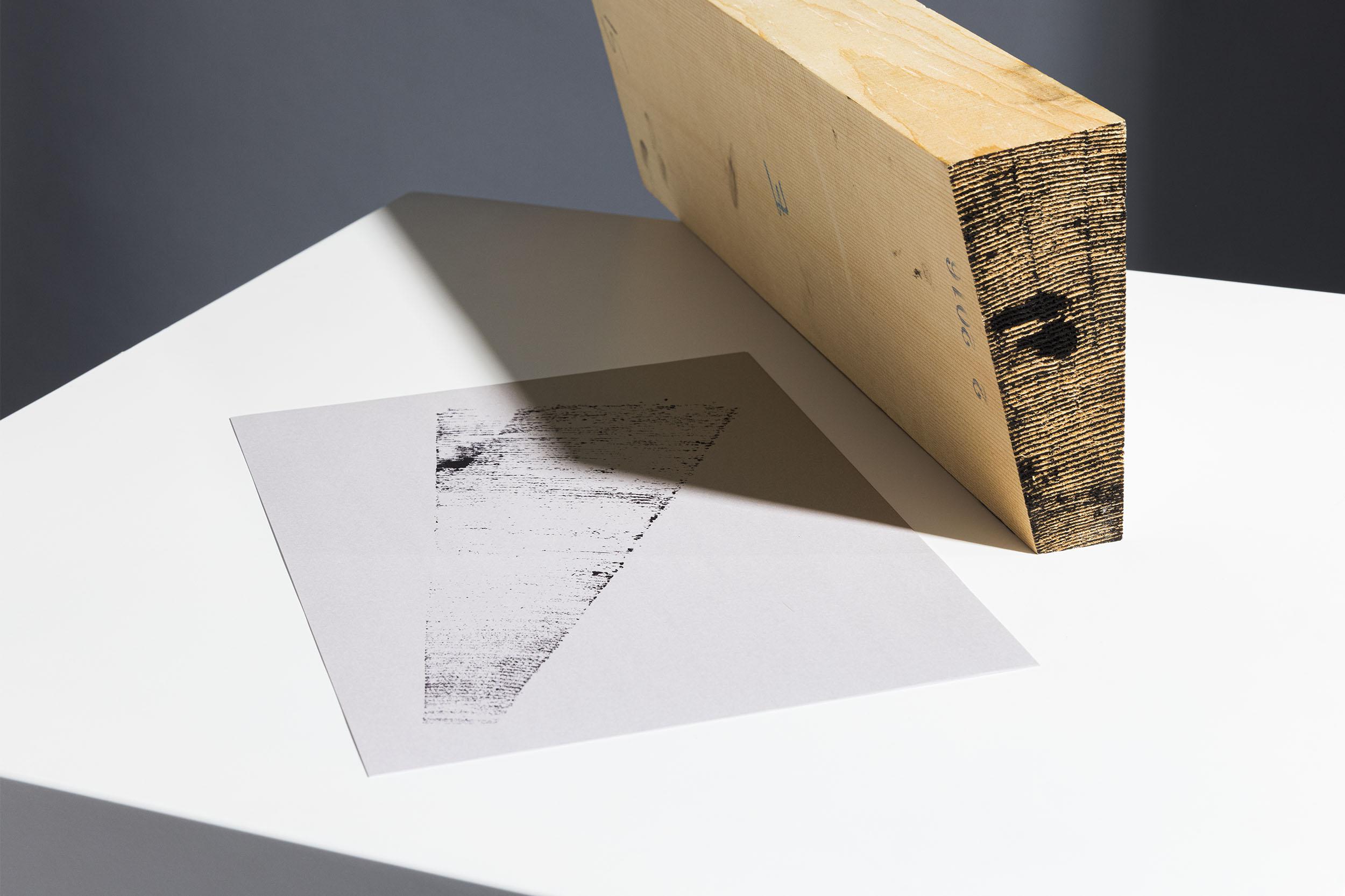 Rückseite Briefbogen mit Key Visual für das Geigenbauatelier Schutter Widmer Krieger und keilförmiges Holzstück, liegend auf weissem Kubus