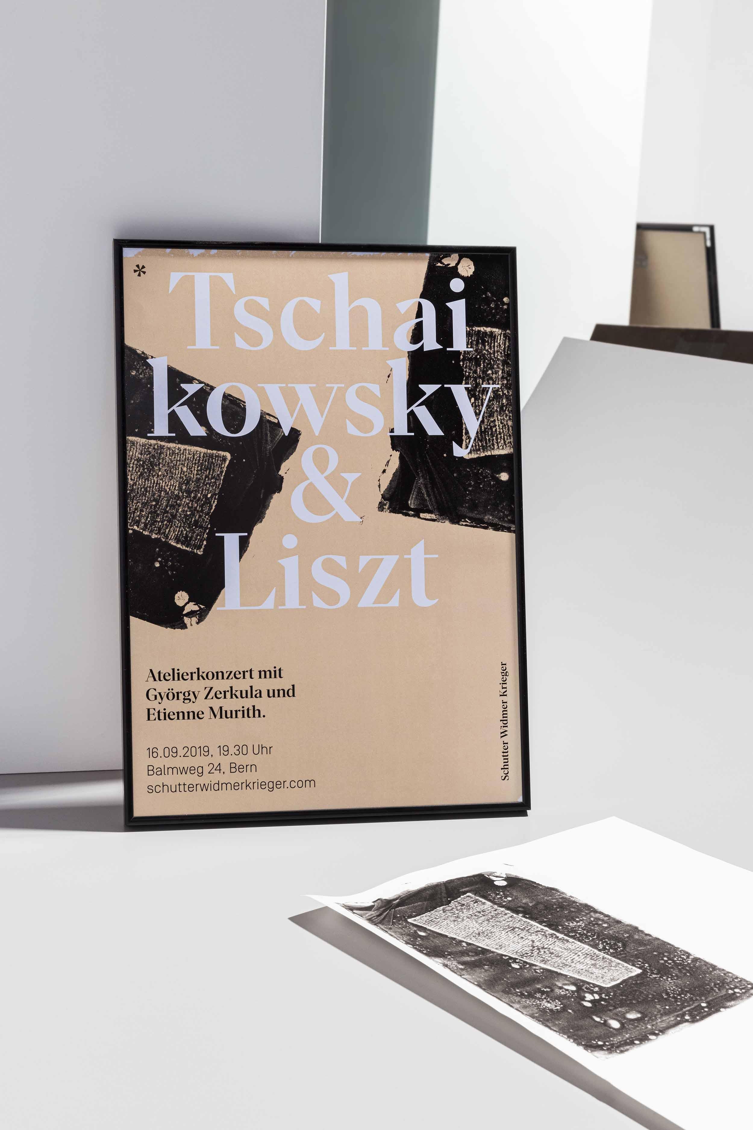 Beigefarbenes Konzertplakat in schwarzem Rahmen und liegender Druck eines Holzkeils