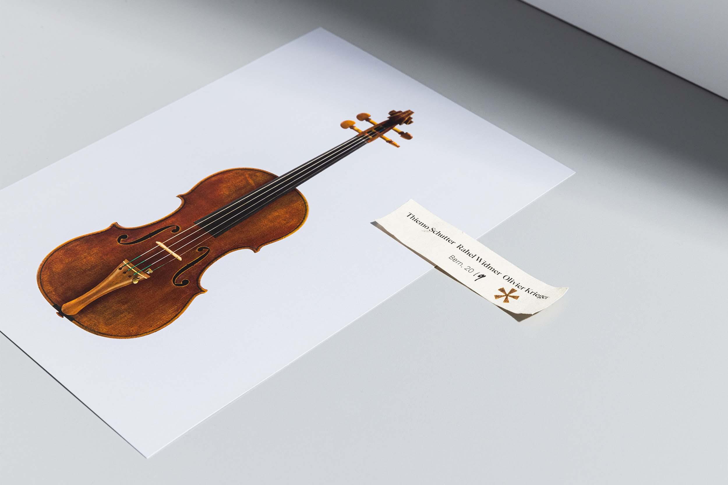 Instrumentenzettel mit eingebranntem Sternsymbol (Asterisk) und Postkarte mit Sujet einer Geige, liegend auf grauem Hintergrund