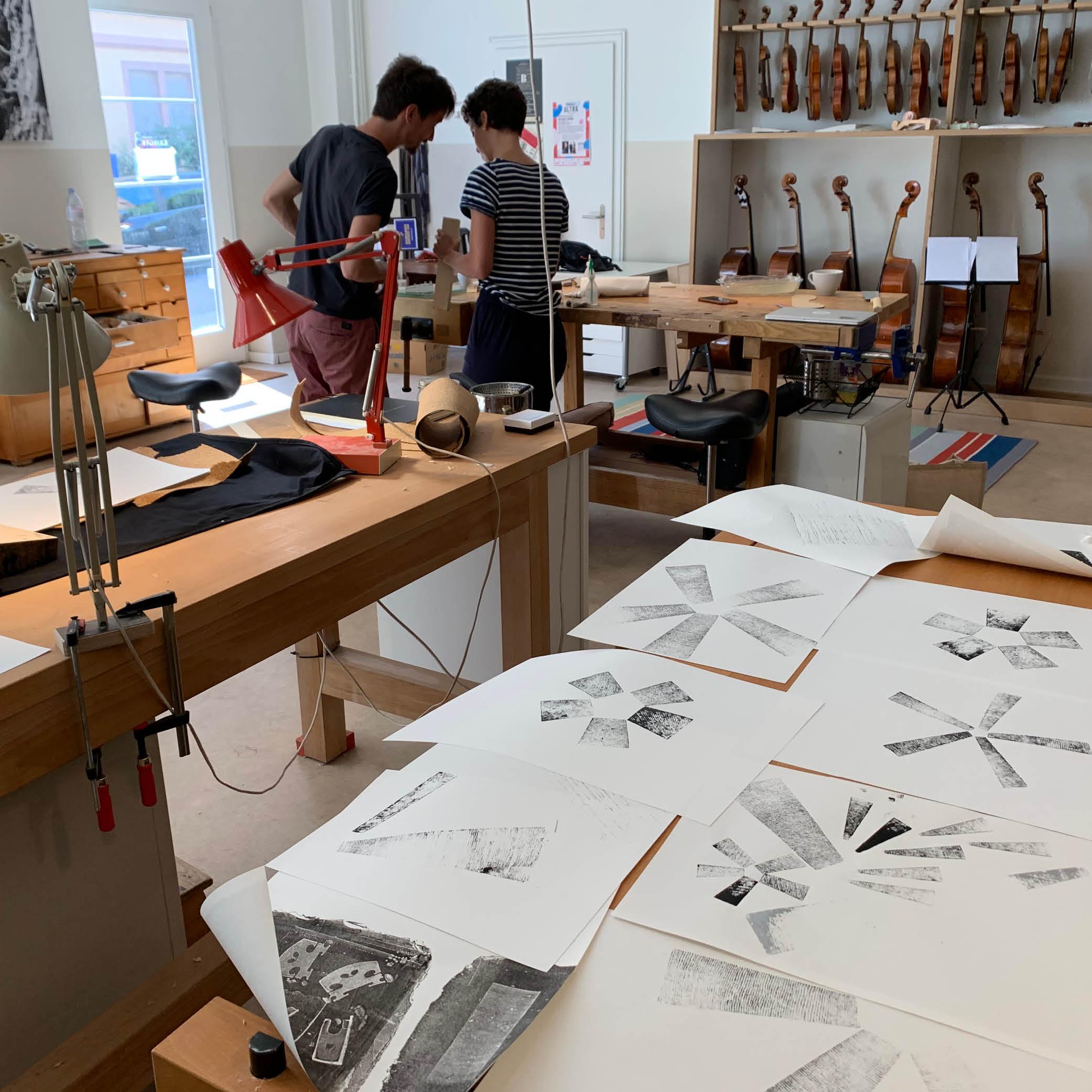Rahel Widmer und Thiemo Schutter drucken mit Holzstücken die Key Visuals für das Geigenbauatelier Schutter Widmer Krieger