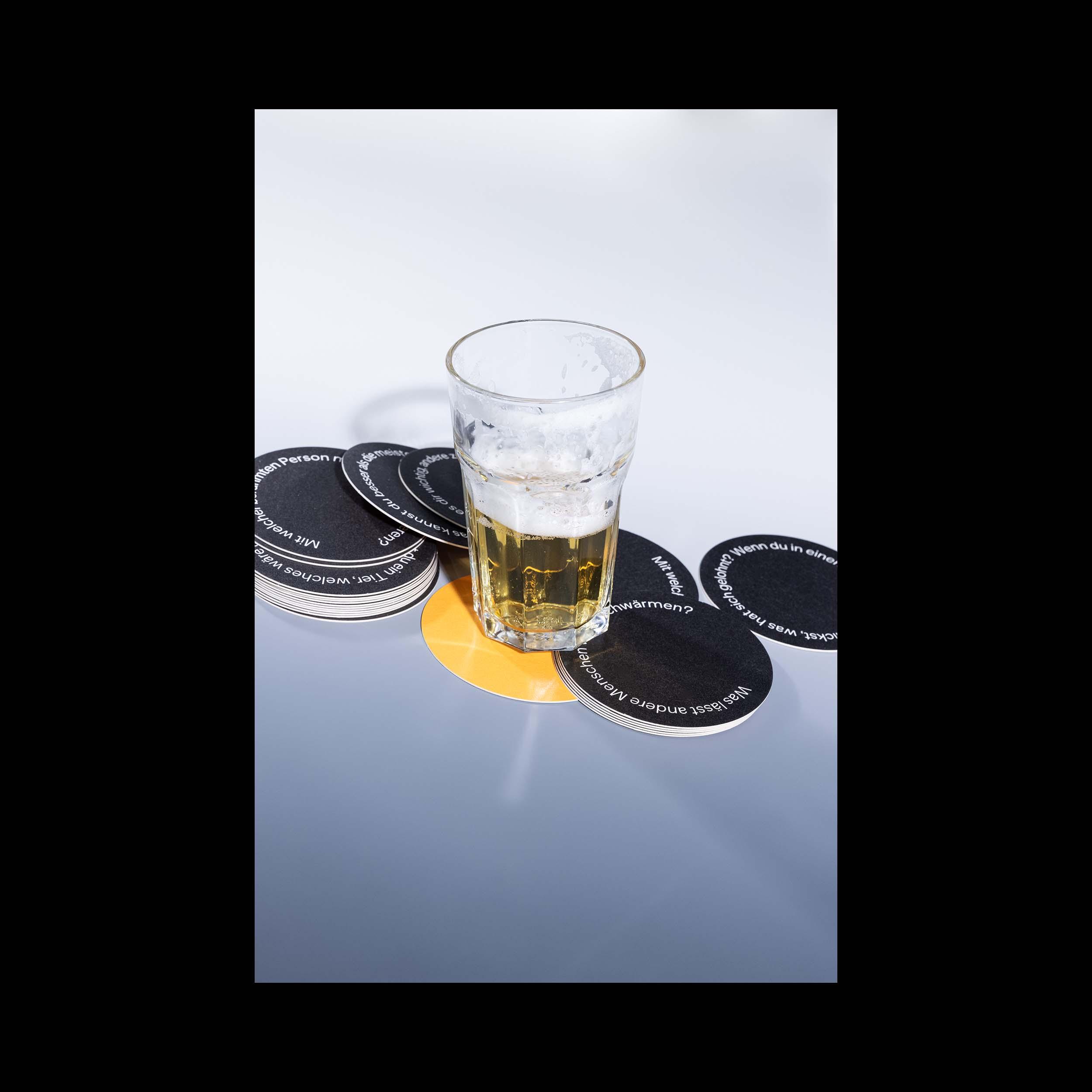 Ein fast ausgetrunkenes Bier mit einigen der Identitäts-Fragekarten von Brink.